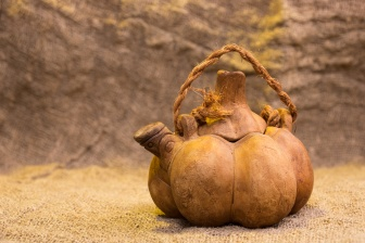 Kettle in the form a pumpkin on background of burlap